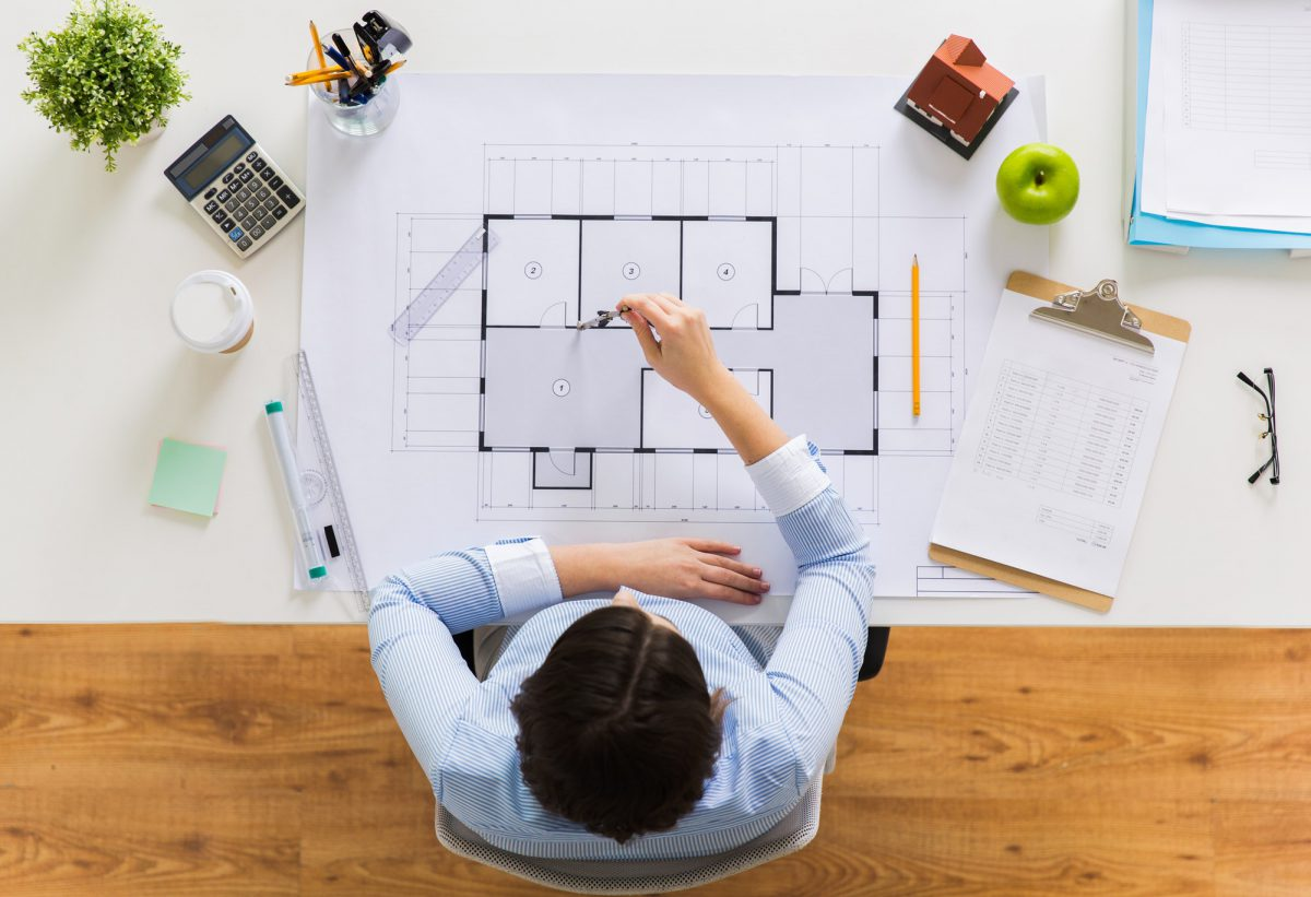 architect with compass measuring blueprint
