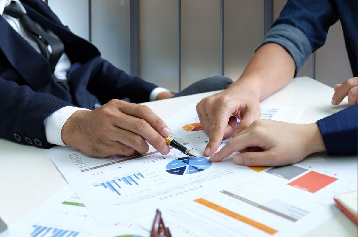 Businessteam are analyzing graphs data.