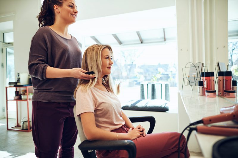 Smiling woman talking with her hairstylist in a salon